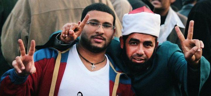 6-un-cristiano-copto-e-un-imam-islamico-alzano-le-dita-in-segno-di-vittoria